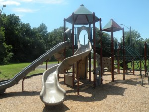 A large playground with benches and picnic pavilion sits at the back of the park